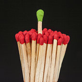 One matchstick standing over from the group, leader concept