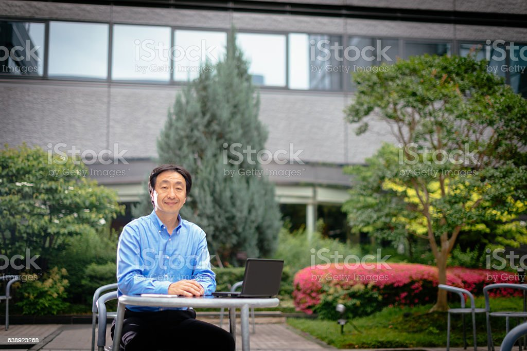 One mature Japanese businessman working on laptop stock photo