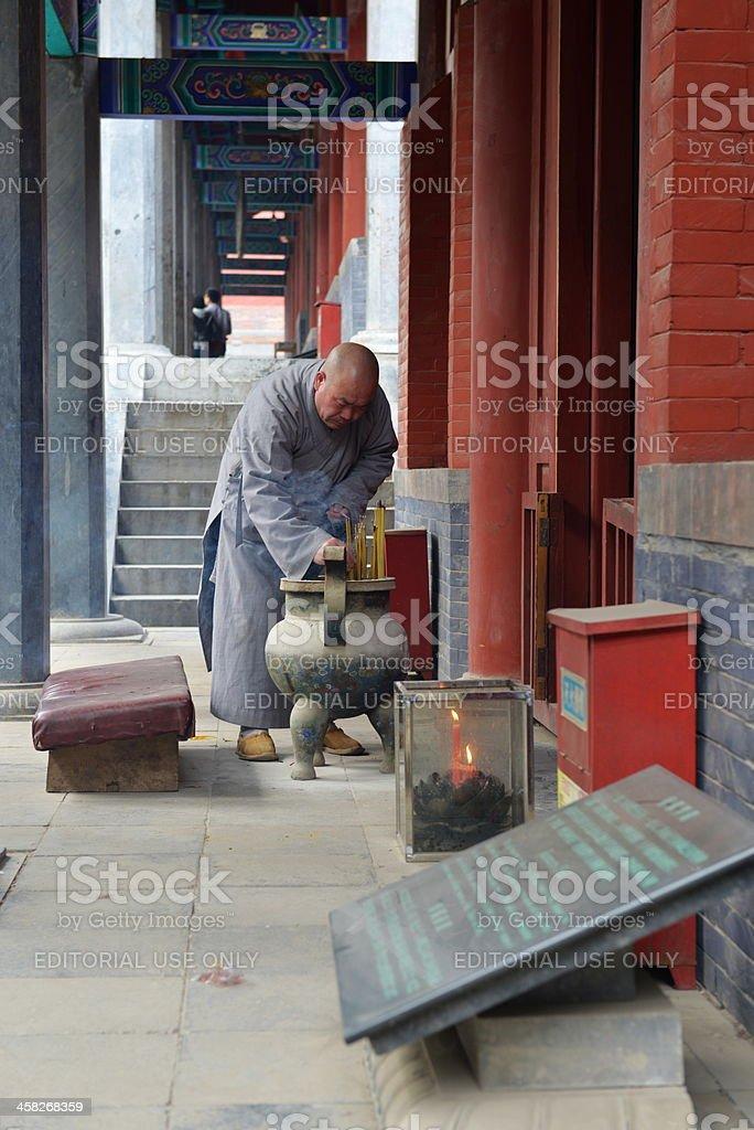 One monk is burning joss sticks stock photo