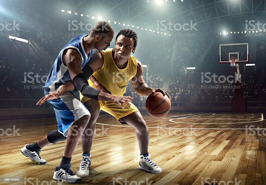 One on one basketball game in the spotlight stock photo