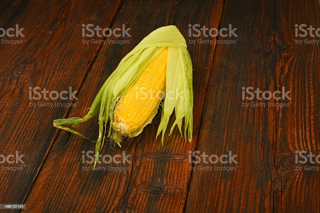 One open corn cob on vintage wooden surface royalty-free stock photo