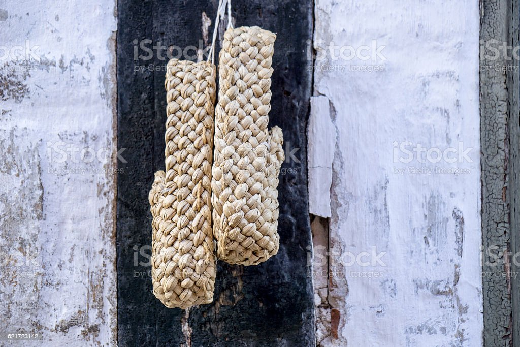 one pair of plaited straw shoes hangs stock photo