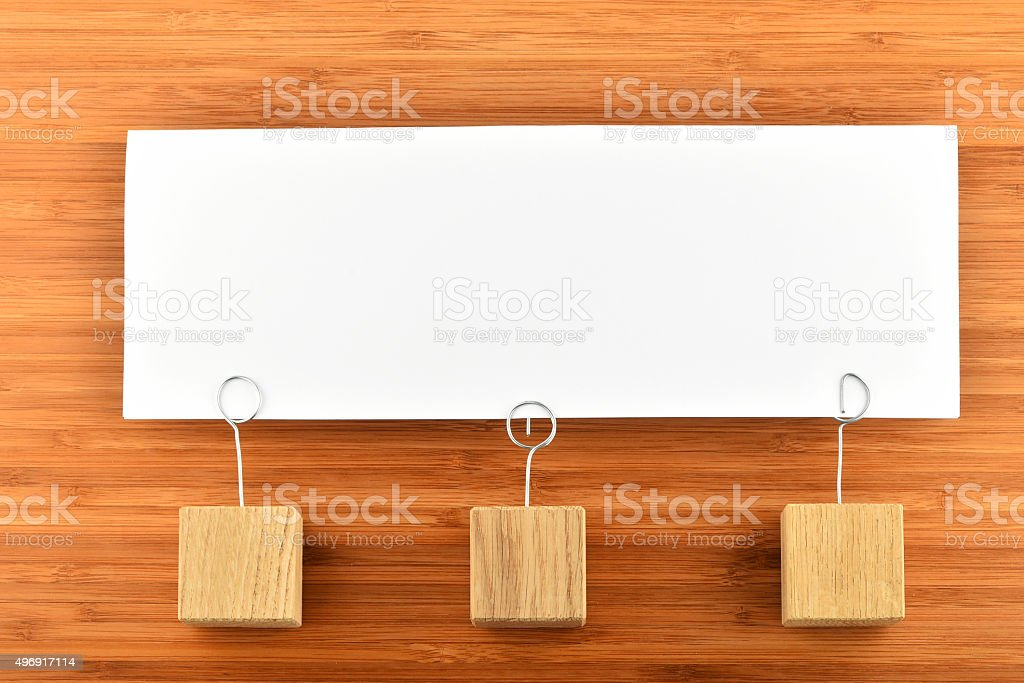 One paper note with three holders isolated on wooden background royalty-free stock photo