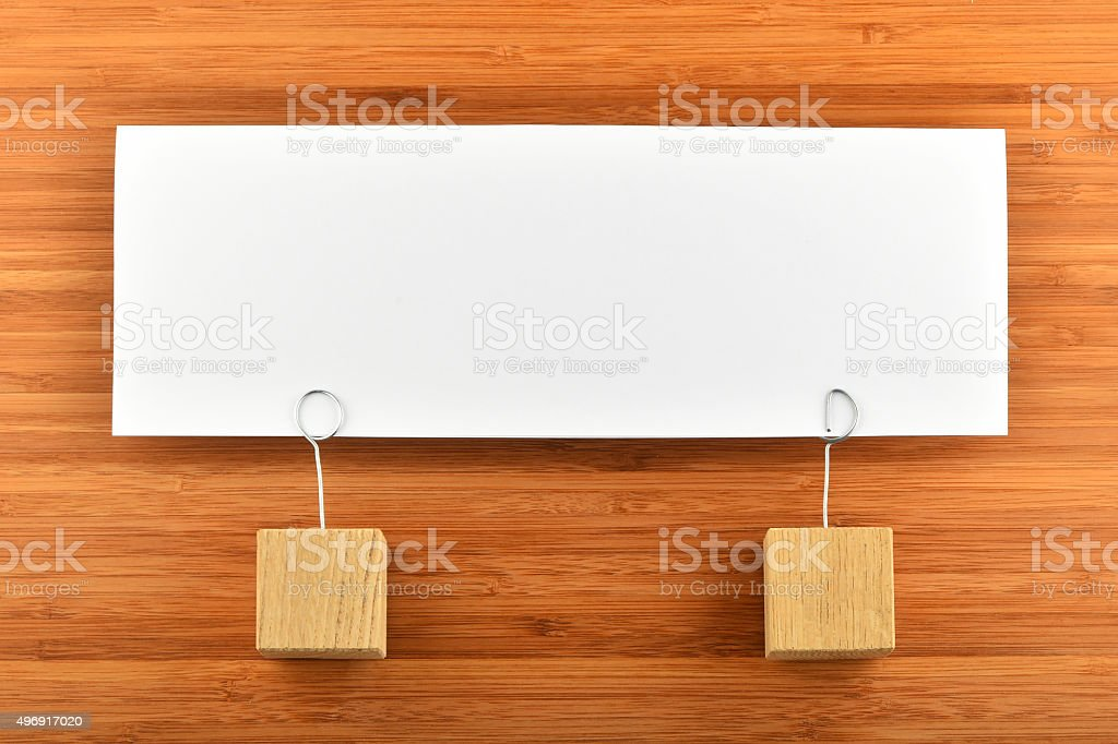 One paper note with two holders isolated on wooden background royalty-free stock photo