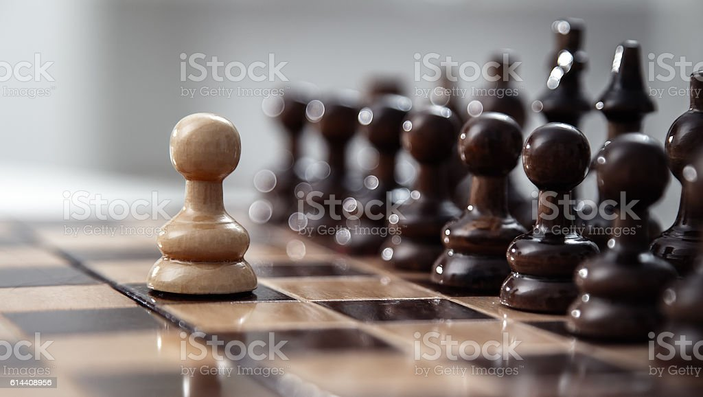 One pawn staying against full set of chess pieces. stock photo