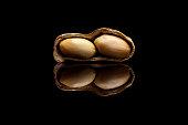 One peeled peanut isolated on black reflective background