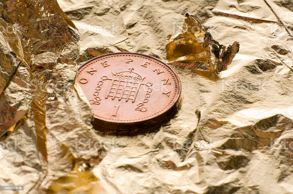 One pence coin on gold leaf stock photo