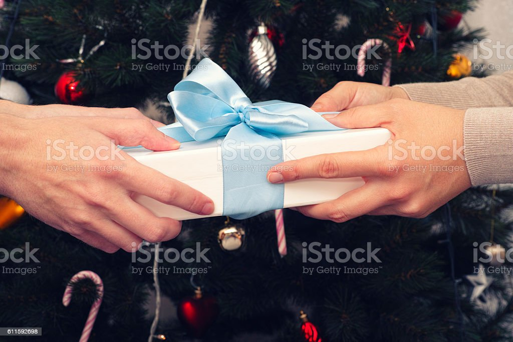 One person giving a christmas gift to another stock photo