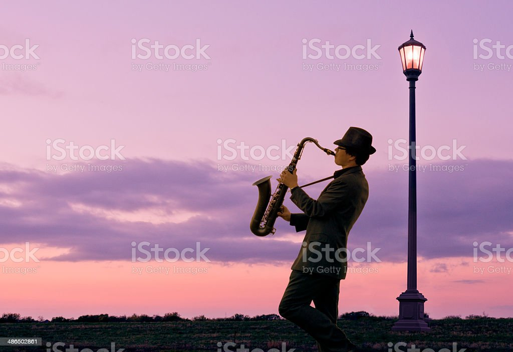 One person playing a saxophone beside Street Lamp royalty-free stock photo