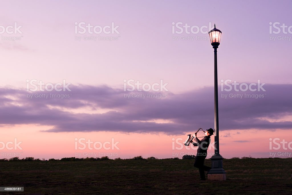 One person playing a tenor saxophone beside Street Lamp royalty-free stock photo