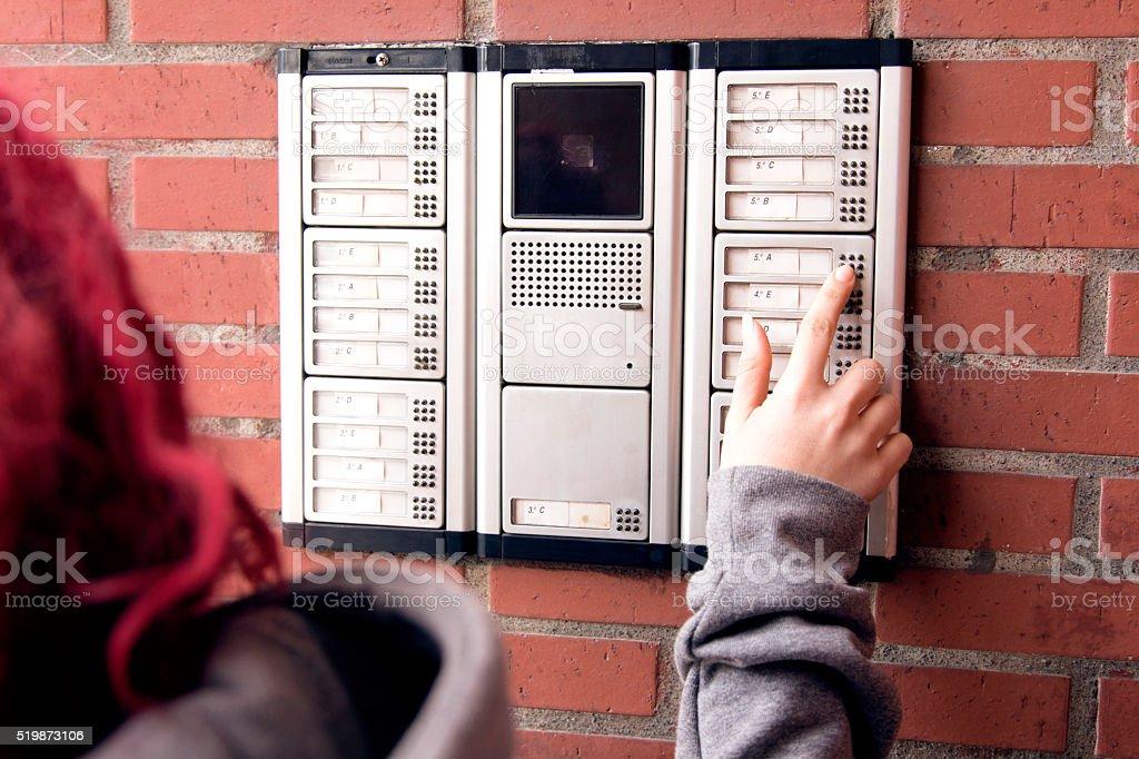 One person presses a button on a intercom stock photo
