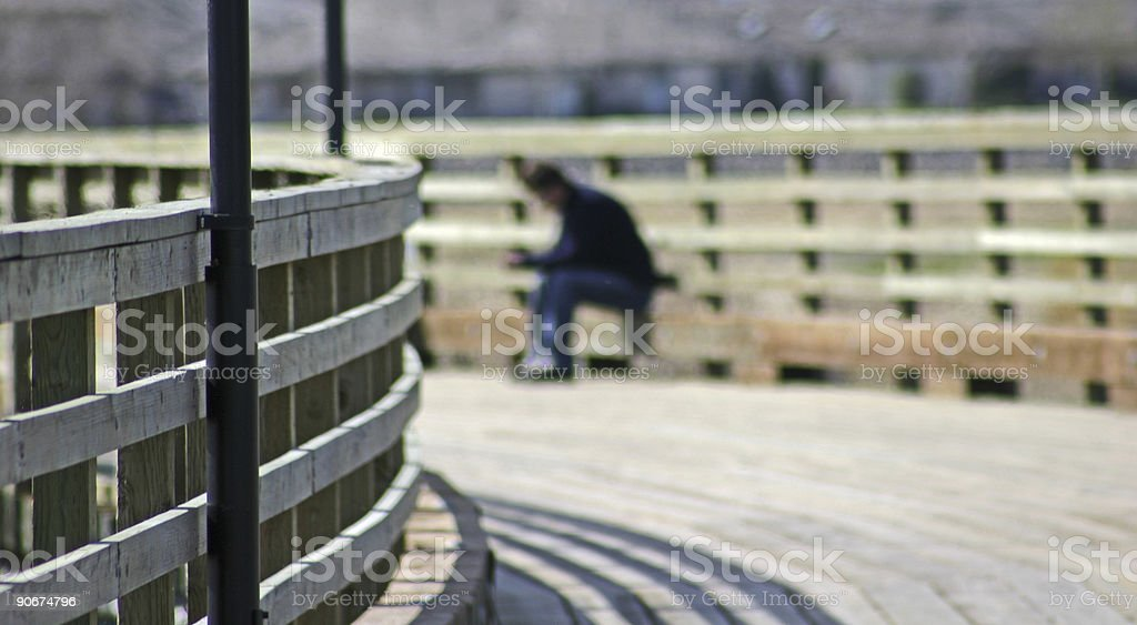 One person sitting on a footbridge thinking royalty-free stock photo