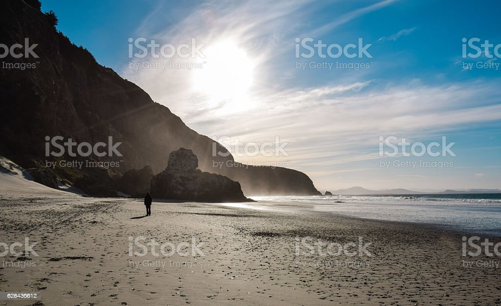 One person walking alone on a beach in New Zealand royalty-free stock photo