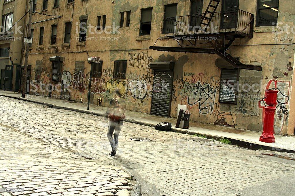 One Person Walking Up Brooklyn DUMBO Cobblestone Backstreet Graffiti royalty-free stock photo