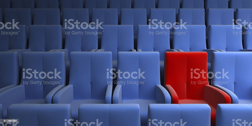 One red chair in an auditorium surrounded by blue chairs stock photo