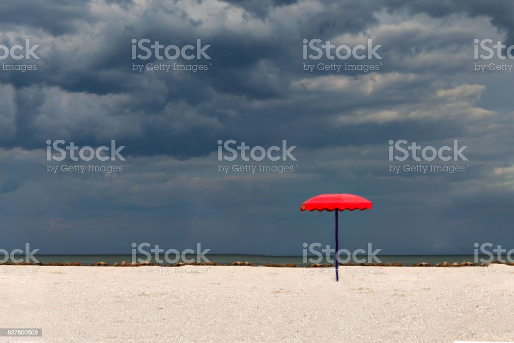 One red parasol on a sandy beach against a stormy sky background stock photo