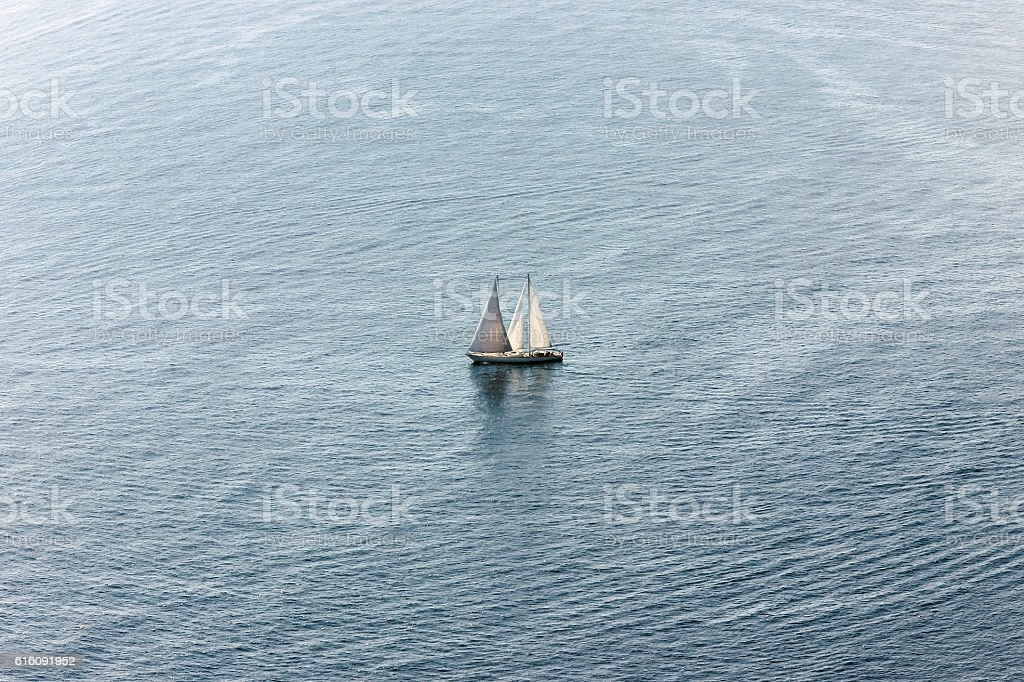 one sailing boat in ocean stock photo