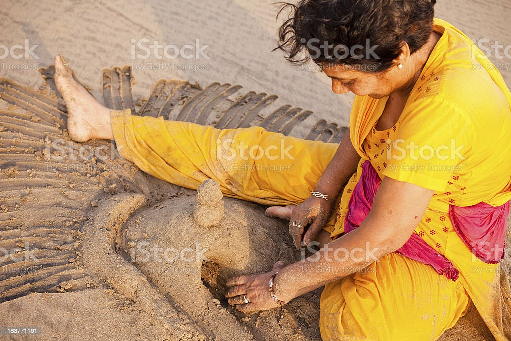 One Senior Indian Woman Enjoying Making Sandcastle on Beach royalty-free stock photo
