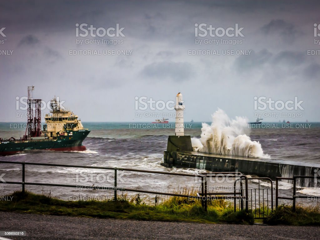 One Ship Approaching Aberdeen Lighthouse During Storm stock photo