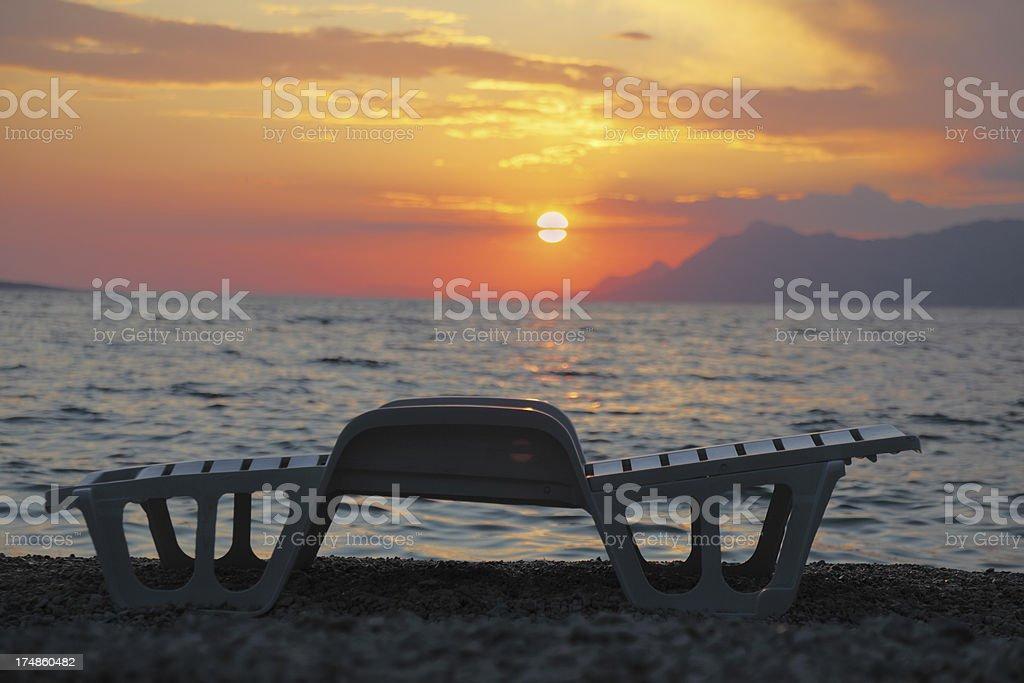 one single white plastic sunbed against mediterranean ocean sunset royalty-free stock photo