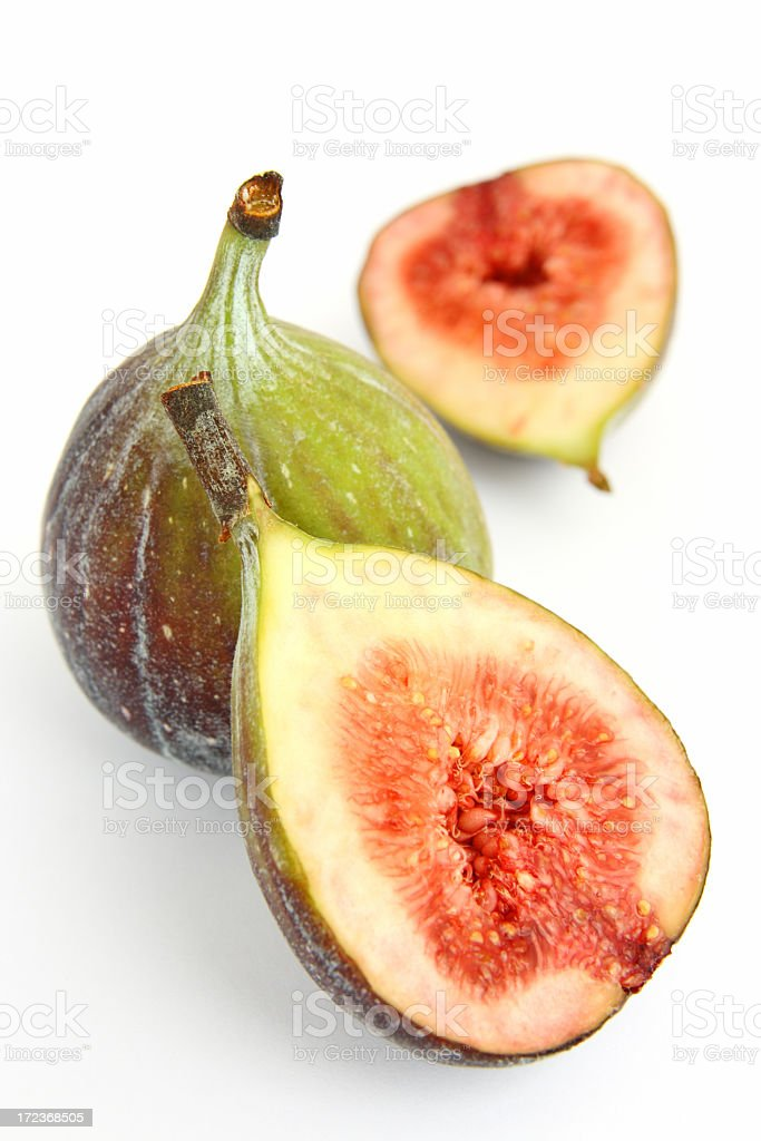 One sliced fig, and one whole fig, on a white background stock photo