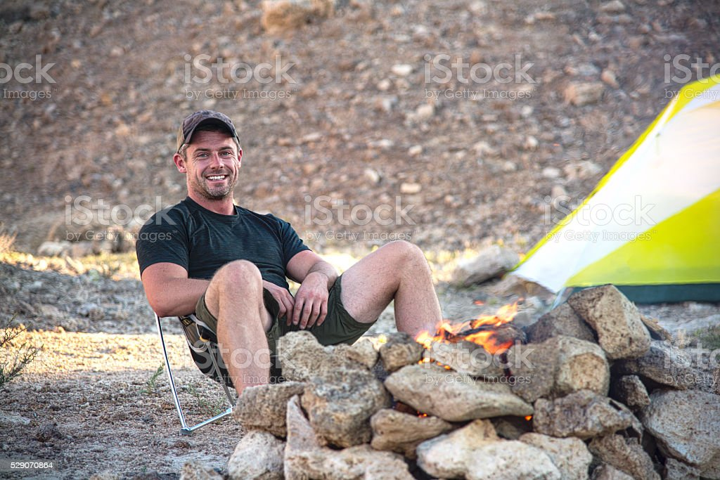 One Smiling Man Sitting by the Campfire stock photo