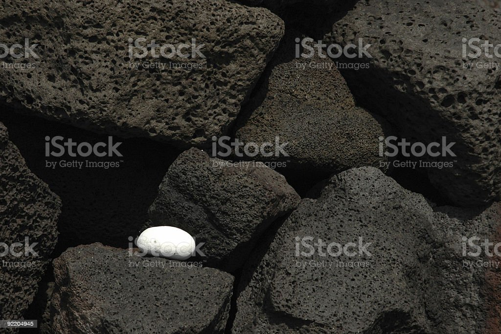 One smooth coral rock on a stack of black lava rock royalty-free stock photo