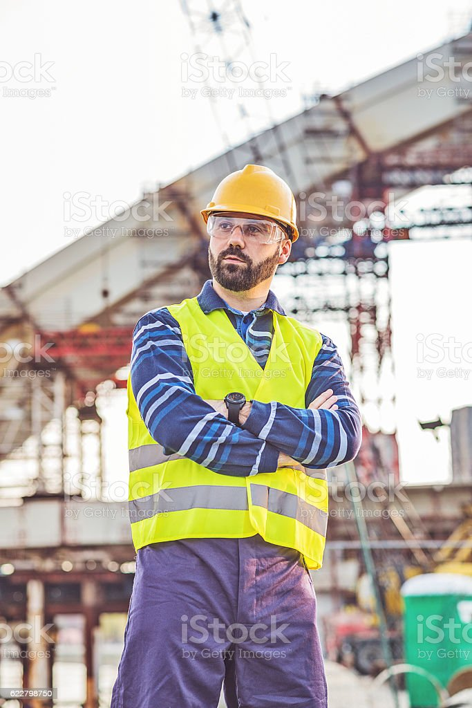 One successful construction worker posing on construction site stock photo