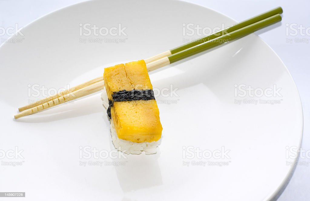 One Tamago yaki nigiri egg omelette sushi with chopsticks royalty-free stock photo