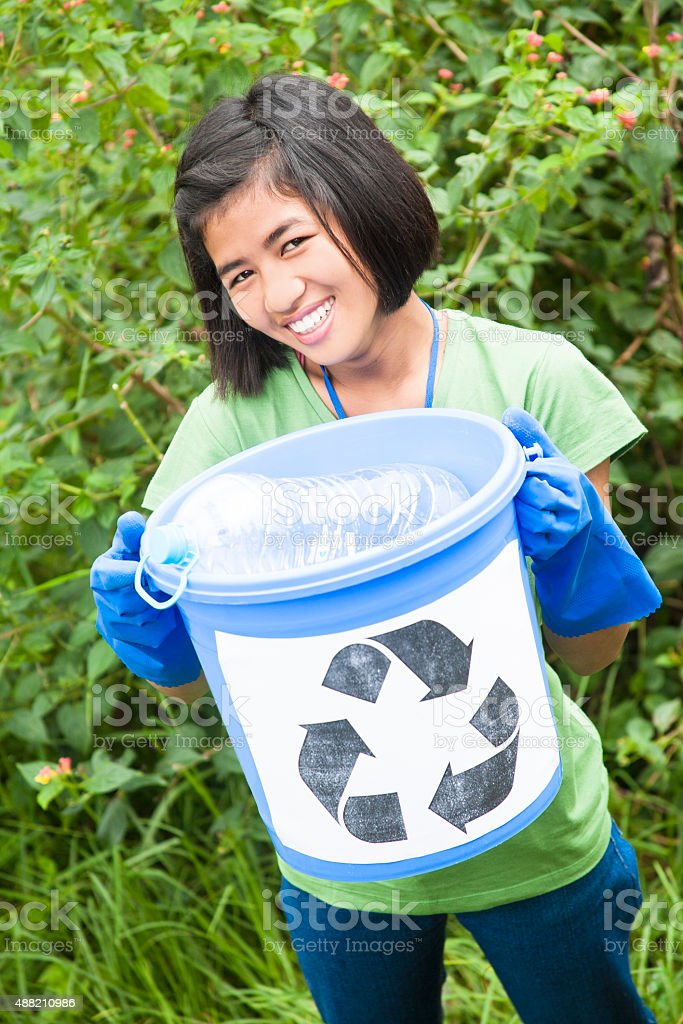 One teenage girl picking up trash to recycle. Nature setting. stock photo