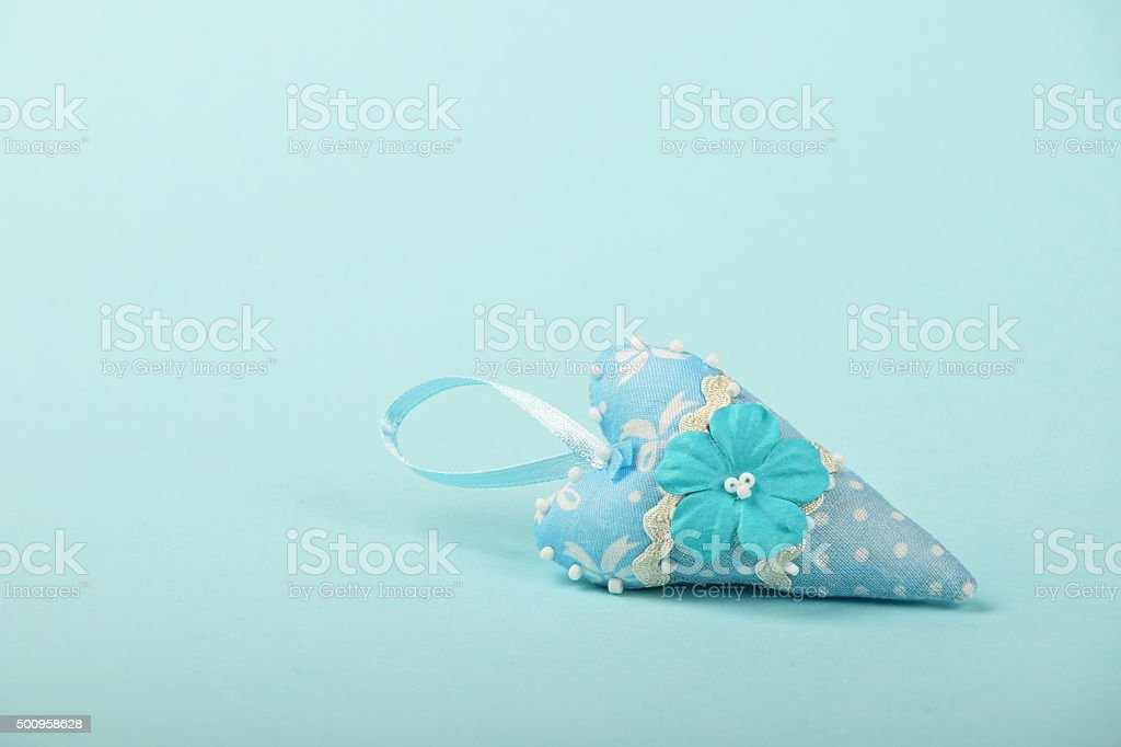 One textile heart with flower on blue background royalty-free stock photo
