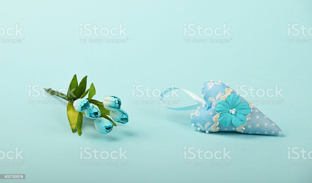One textile heart with flowers on blue background royalty-free stock photo