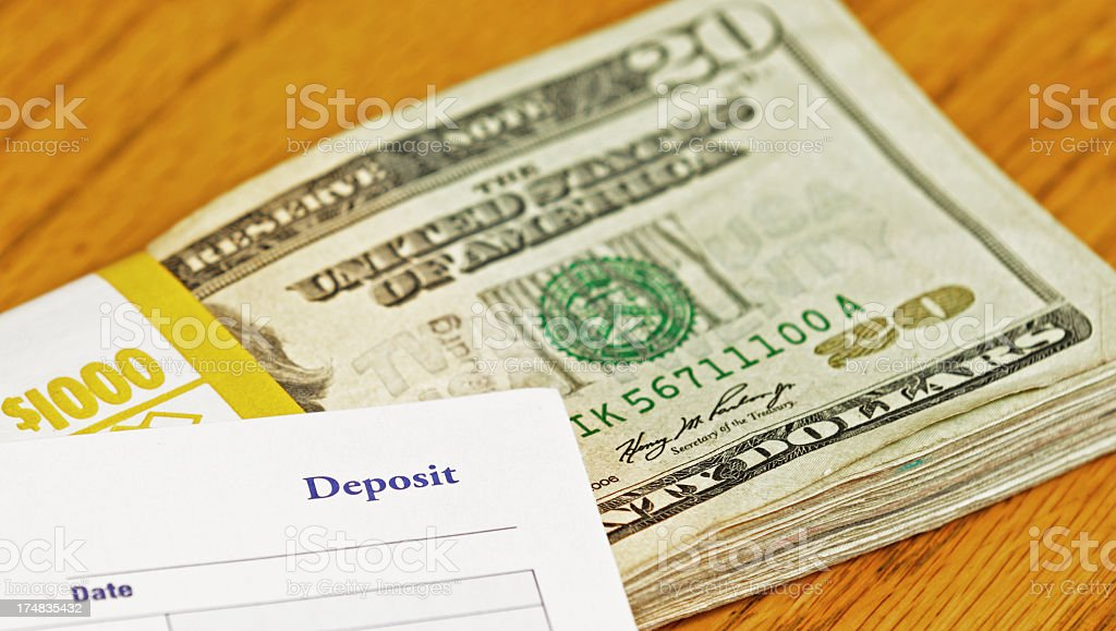 One Thousand Dollars and Bank Deposit Slip stock photo