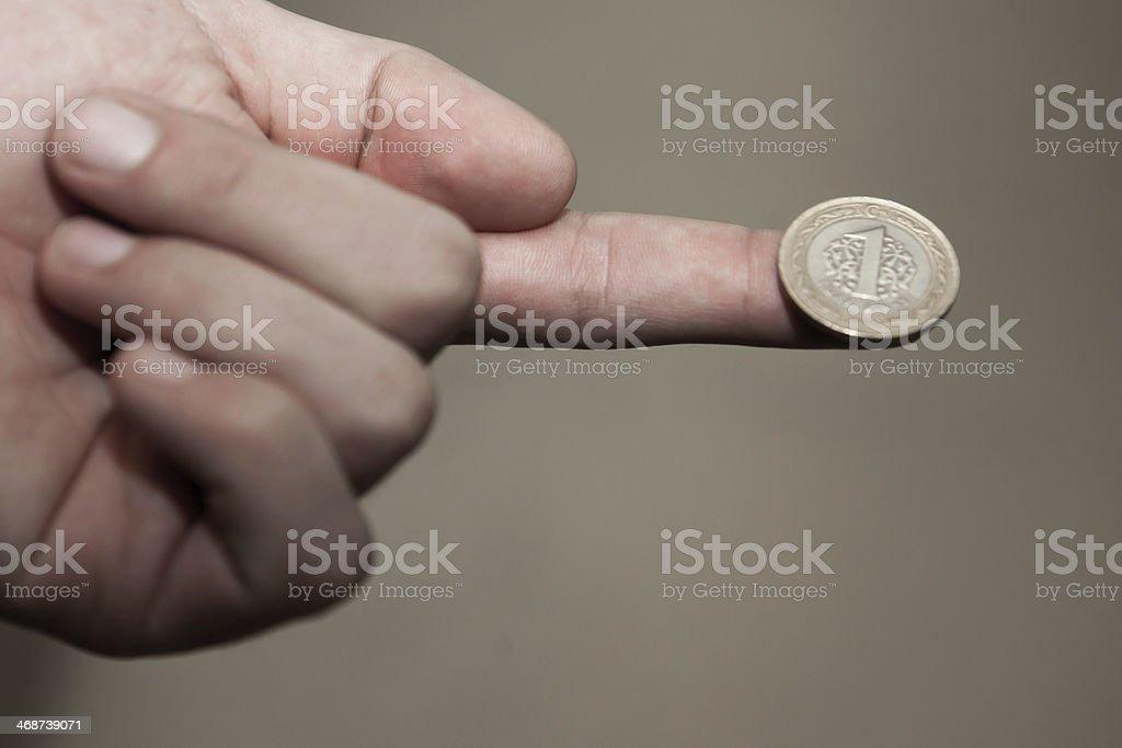 One Turkish Lira on human finger stock photo