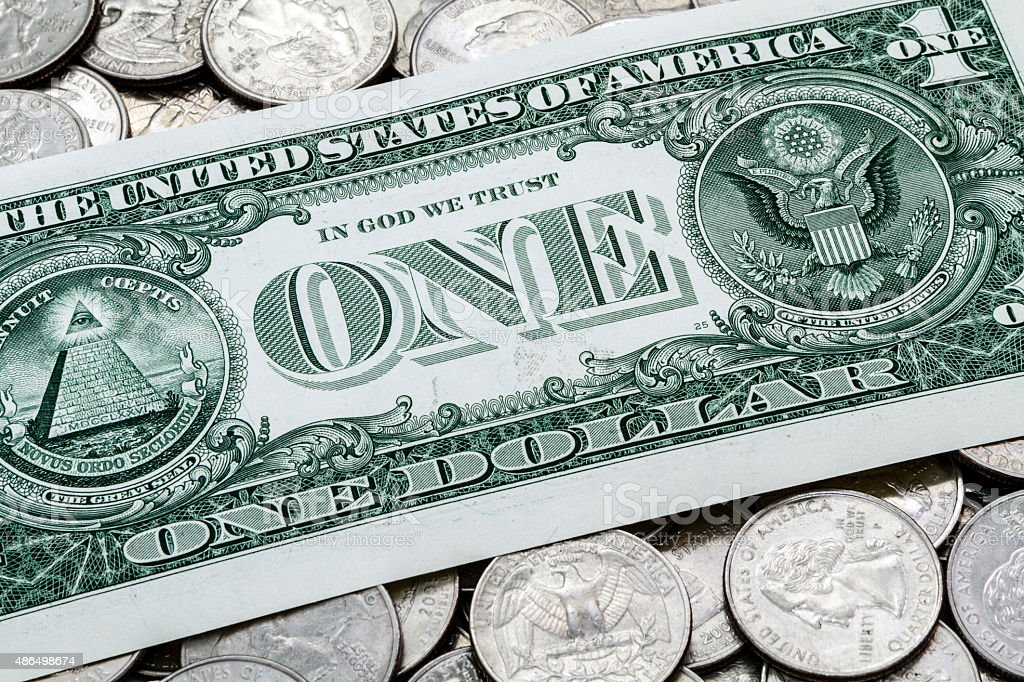 One USA Dollar Bill On A Pile Of Quarters stock photo
