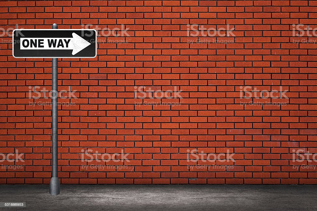 One way  road sign on brick wall stock photo