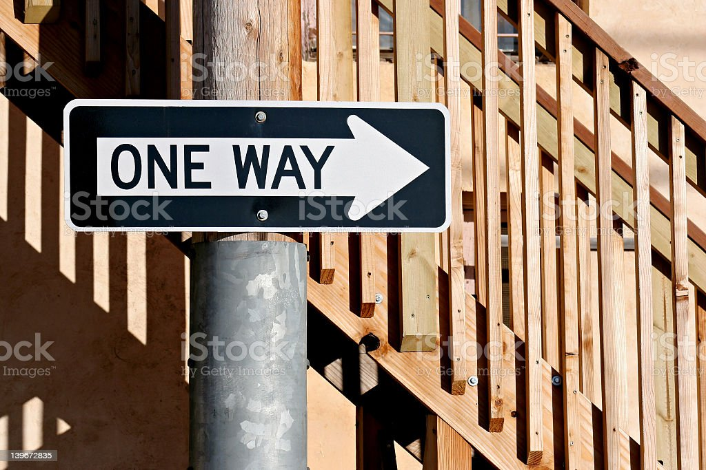 One way sign on the pole near wooden stairs stock photo