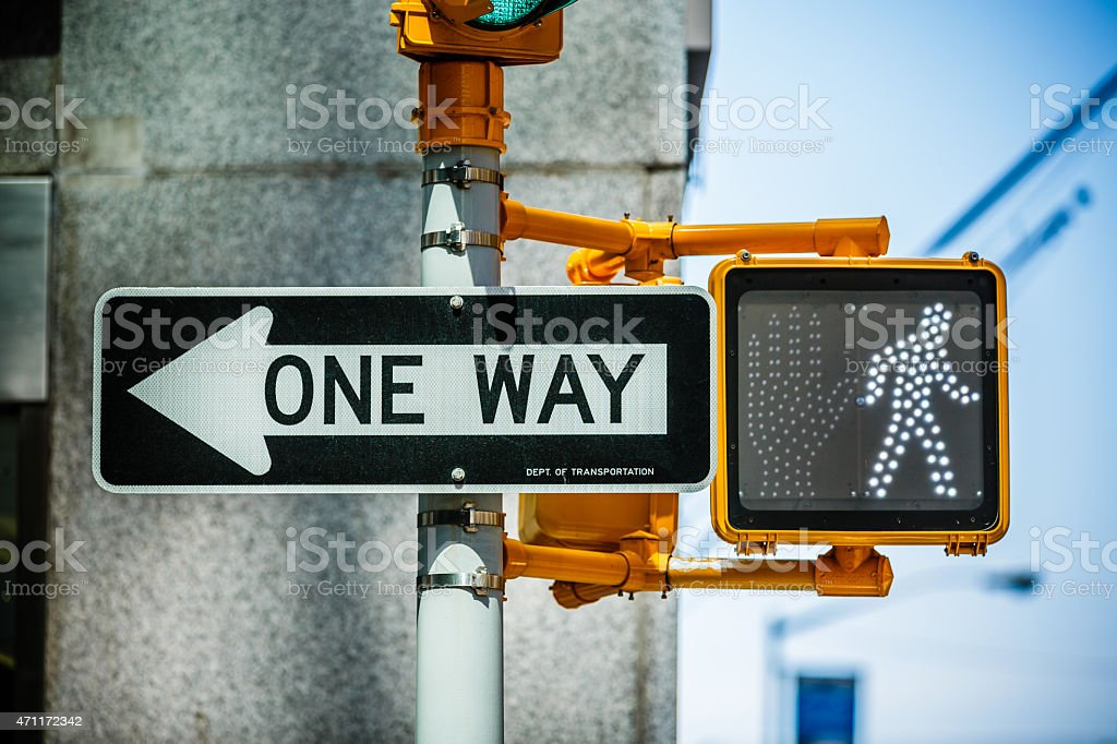 One way sign with green pedestrian traffic light stock photo