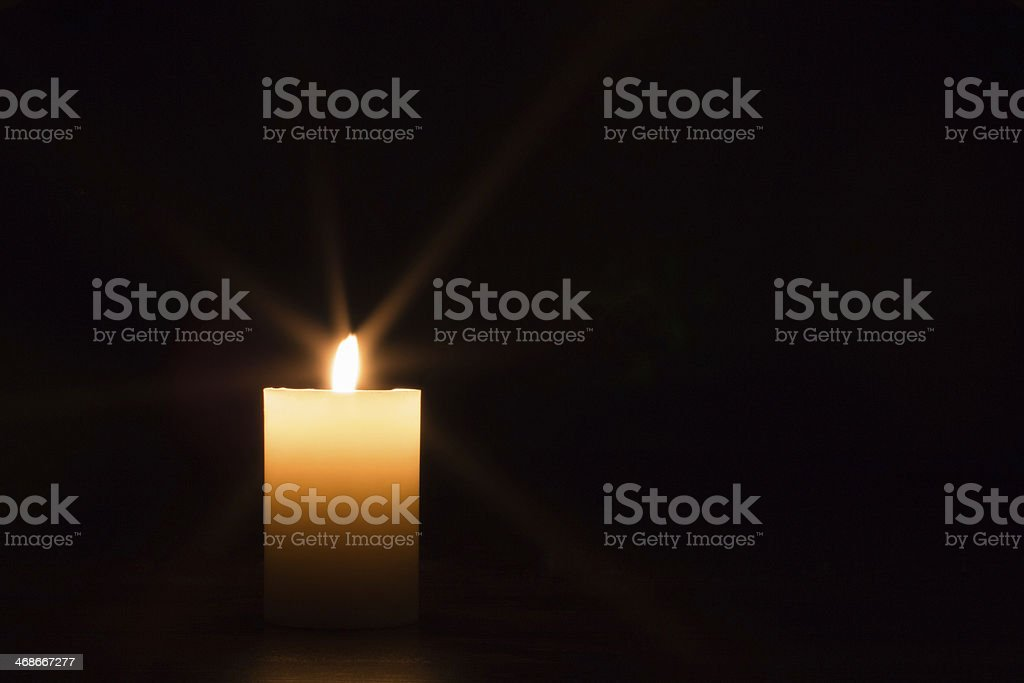 One white candle and black background stock photo