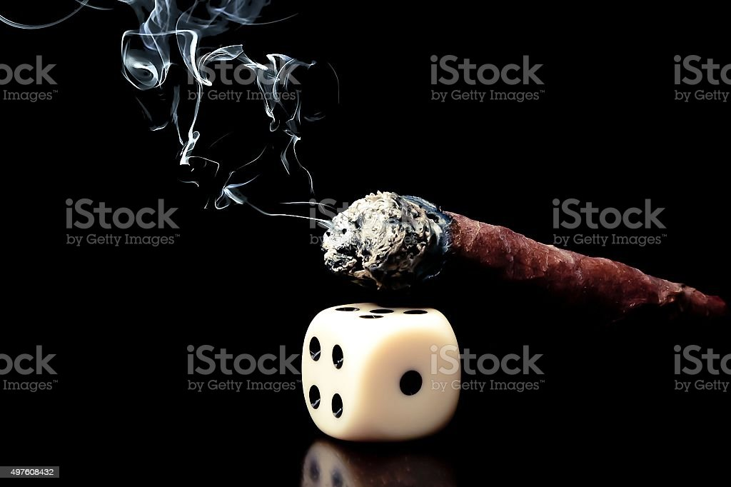 one white dice and cigar with smoke on black background stock photo