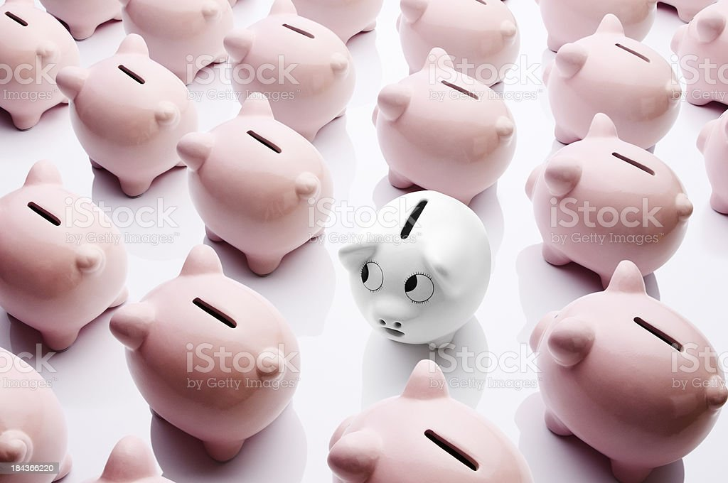 One white piggy bank facing in different direction to others stock photo