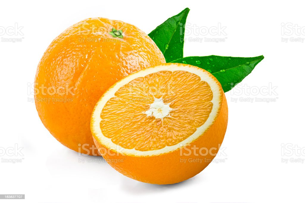 One whole and a sliced half of an orange with green leaves stock photo