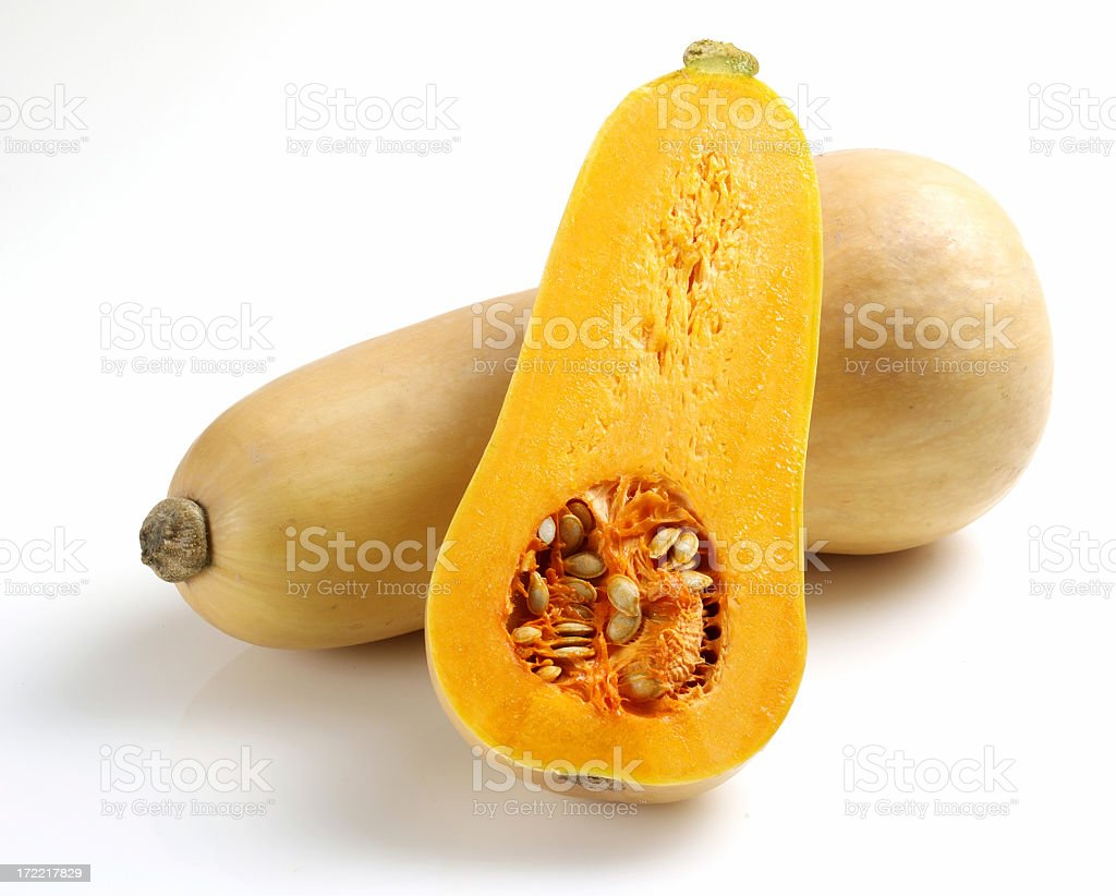 One whole and one half butternut squash sliced open stock photo