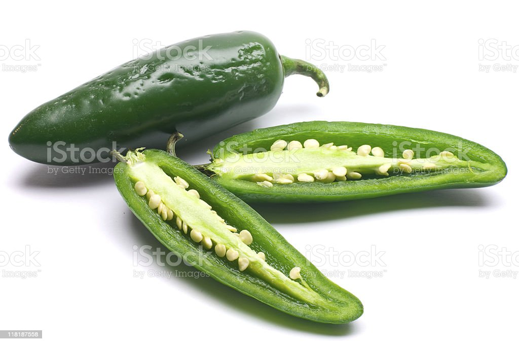 One whole green Jalapeno pepper and one sliced in two royalty-free stock photo