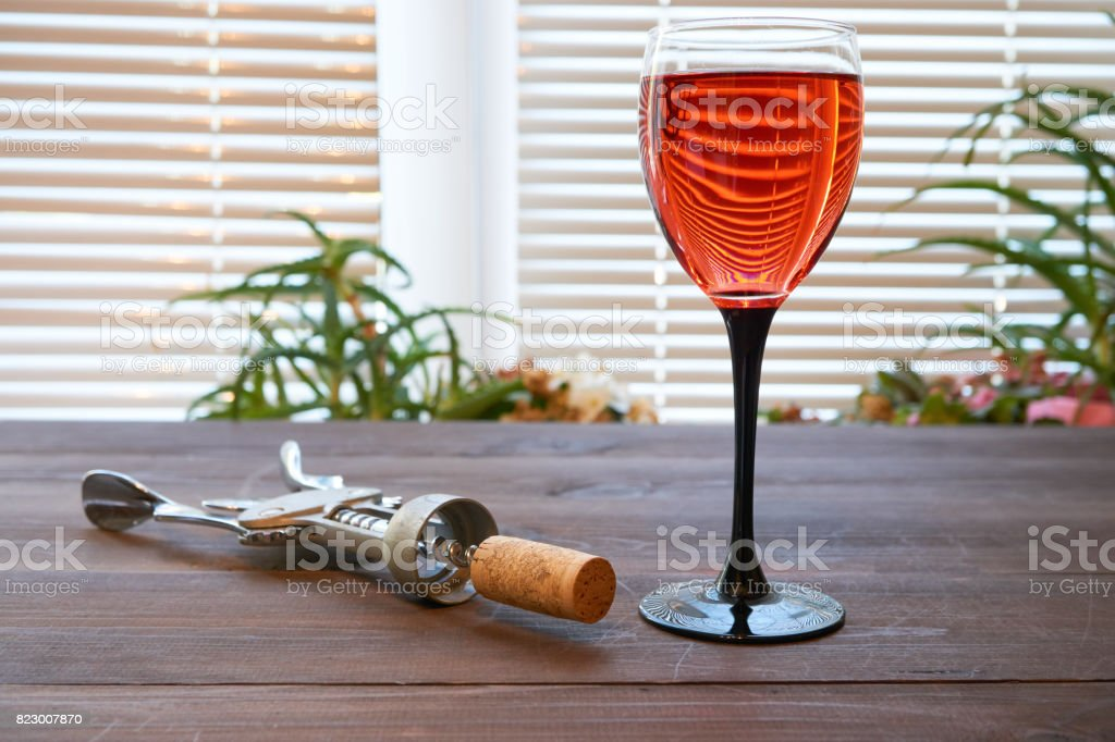 one wineglass of red pink wine on dark desk stock photo
