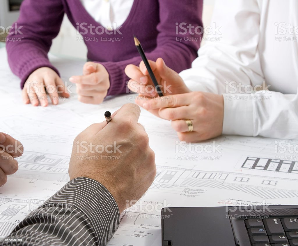One woman and two men at a desk looking over plans royalty-free stock photo