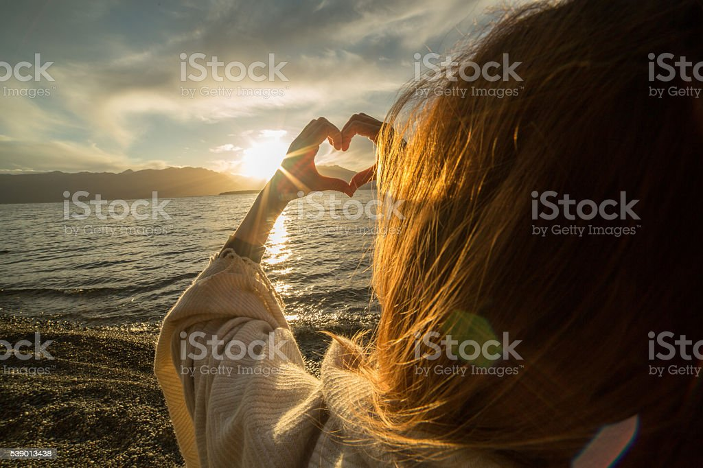 One woman by the lake making heart shape finger frame stock photo