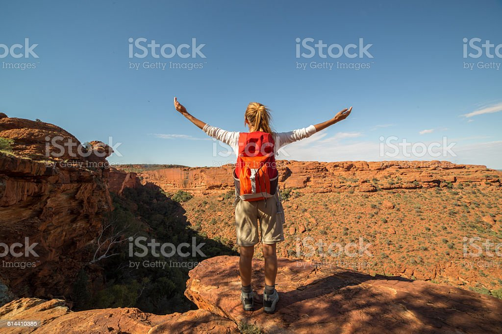 One woman hiking enjoys freedom on mountain top stock photo