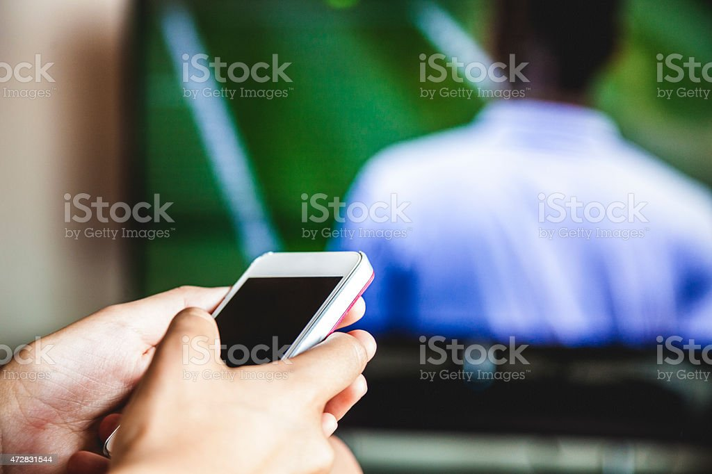 One woman holding mobile phone during a soccer match stock photo