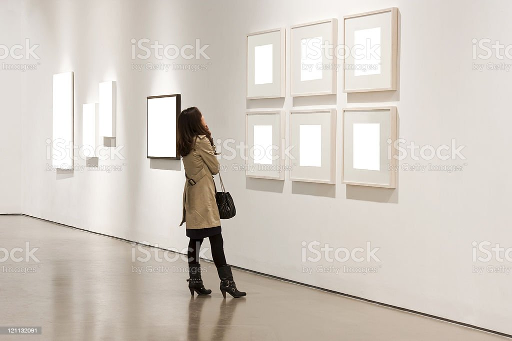 One woman looking at white frames in an art gallery royalty-free stock photo